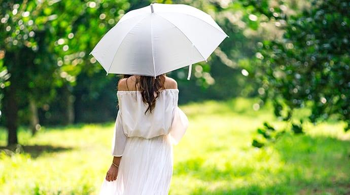 Een vrouw die tijdens warm weer met een parasol loopt omdat ze last heeft van jeukende huid